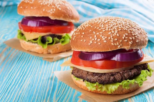 Twee zelfgemaakte cheeseburgers met runderpasteitjes en verse salade op seasame broodjes, gesered op blauwe houten tafel.