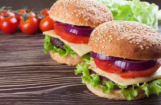 Twee zelfgemaakte cheeseburgers met runderpasteitjes en verse salade op seasame-broodjes, gesered op bruine houten tafel.