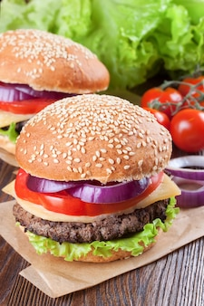Twee zelfgemaakte cheeseburgers met runderpasteitjes, verse salade, tomaten en ui op seasame broodjes, geserveerd op bruine houten tafel.