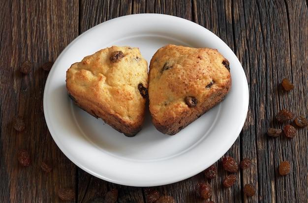 Twee zelfgemaakte muffins met rozijnen in hartvorm