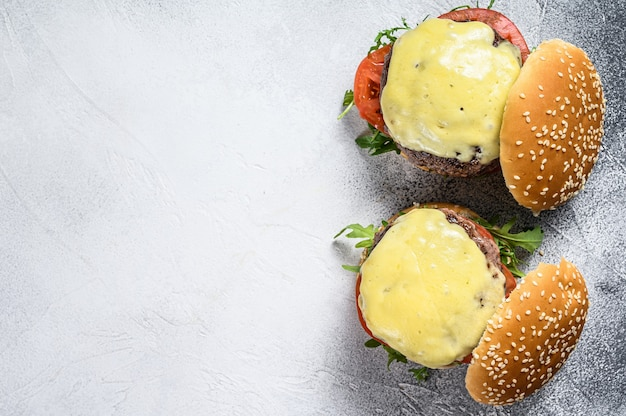 Twee zelfgemaakte rundvleesburgers met kaas, groenten, ui. witte achtergrond. bovenaanzicht.