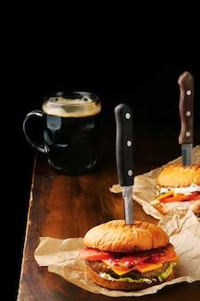 Twee zelfgemaakte smakelijke hamburgers met grote rundvlees, kaas, tomaat en donkere bierpul op houten tafel en zwarte tafel.