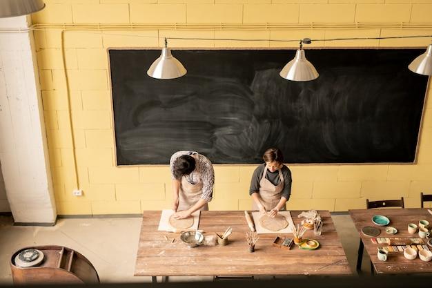 Twee zelfstandige ambachtslieden die met uitgerolde klei werken terwijl ze in hun werkplaats aan een houten tafel staan