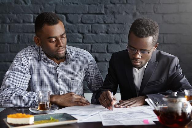 Twee zelfverzekerde afro-amerikaanse zakenlieden gekleed formeel met ernstige geconcentreerde blikken