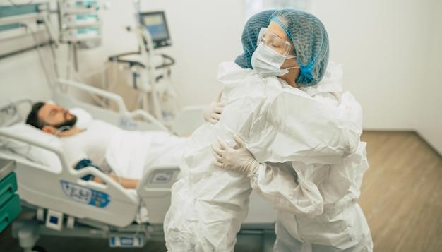Twee zelfverzekerde artsen in beschermende veiligheidspakken staan op de achtergrond van een patiënt met coronavirus