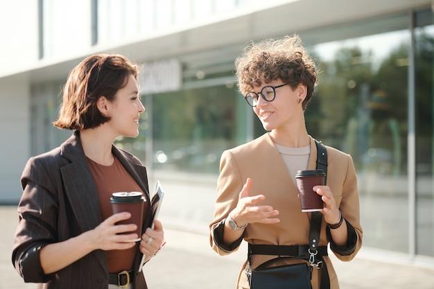 Twee zelfverzekerde collega's in slimme vrijetijdskleding bespreken werkpunten in een stedelijke omgeving terwijl ze langs het zakencentrum lopen en een drankje drinken