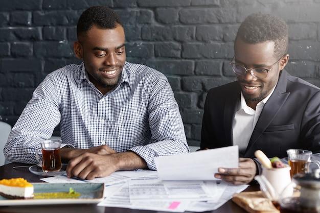 Twee zelfverzekerde, donkere leidinggevenden glimlachen blij nadat ze een winstgevende deal hebben getekend