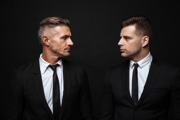 Twee zelfverzekerde knappe zakenlieden die een pak dragen dat geïsoleerd over een zwarte muur staat, elkaar aankijkend