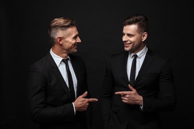 Twee zelfverzekerde knappe zakenlieden die een pak dragen dat geïsoleerd over een zwarte muur staat en naar elkaar wijst