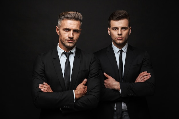Twee zelfverzekerde knappe zakenlieden die een pak dragen dat geïsoleerd over een zwarte muur staat, met gevouwen armen
