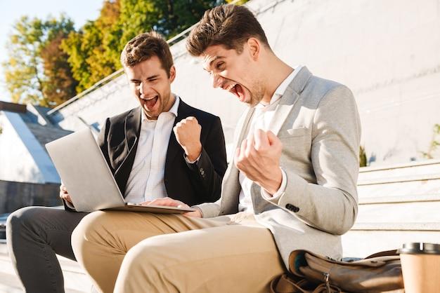 Twee zelfverzekerde zakenlieden met behulp van laptopcomputer zittend op een bankje buiten, succes vieren