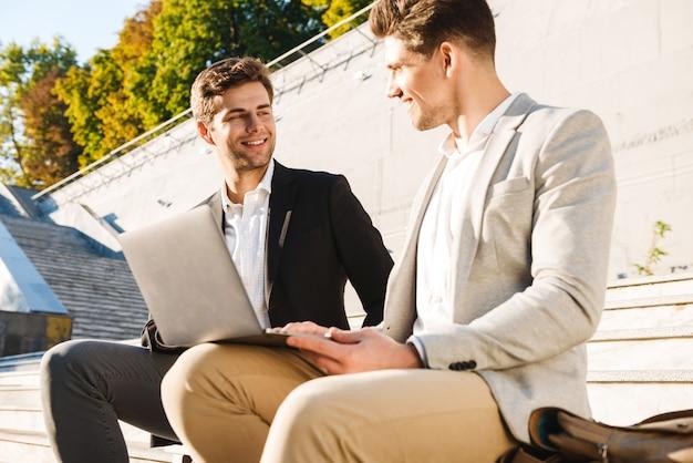 Twee zelfverzekerde zakenlieden met behulp van laptopcomputer zittend op een bankje buiten