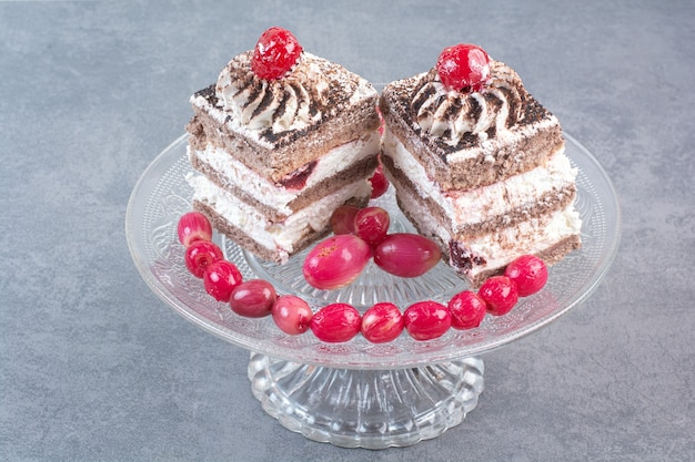 Twee zoete heerlijk stuk taarten met rozebottels op glazen plaat.