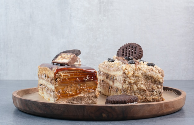 Twee zoete heerlijke stuk taarten met koekjes op een houten bord.