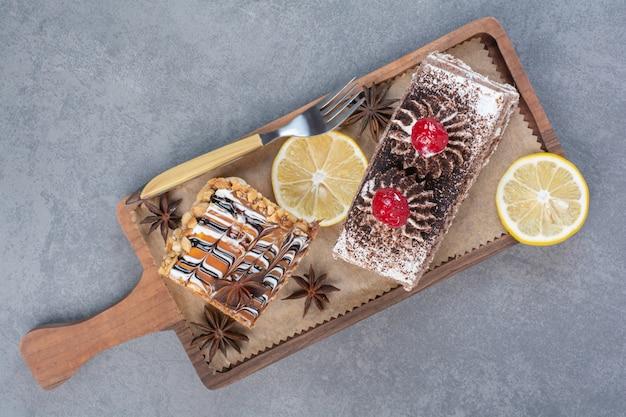 Twee zoete heerlijke stuk taarten met steranijs op houten bord.