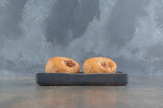 Twee zoete taarten op een houten bord