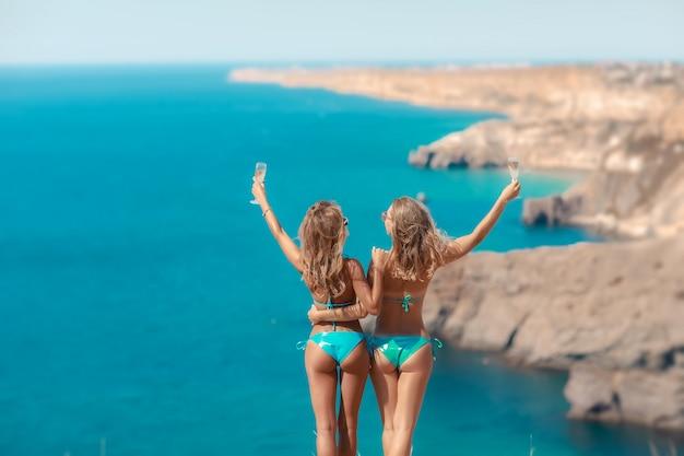 Twee zomer vriendinnen in bikini badmode staan hand in hand op een berg boven de zee