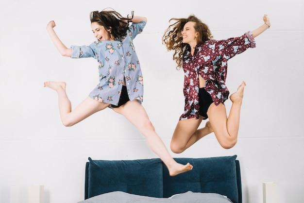 Twee zorgeloze vrouw springen op bed