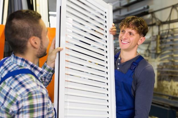 Twee zorgvuldige werklieden die vensters inspecteren