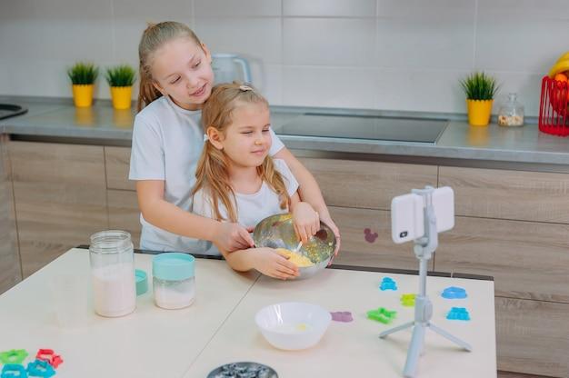Twee zusjes bloggers koken in de keuken en maken een culinaire video op een smartphone.