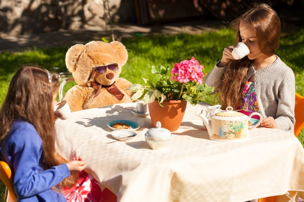Twee zusjes die engels ontbijten met teddybeer op het erf