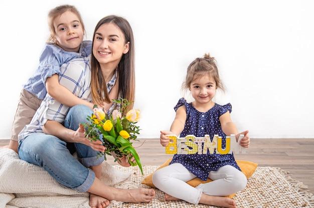 Twee zusjes feliciteren hun moeder met happy mother's day. kinderen knuffelen en zoenen moeder.
