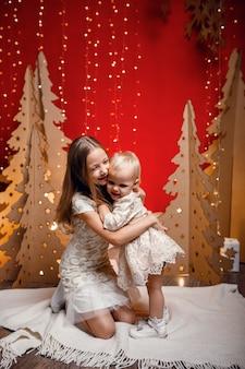 Twee zusjes knuffelen tegen de achtergrond van rode kerstversieringen. idee en concept van goede en vriendschappelijke betrekkingen in het gezin