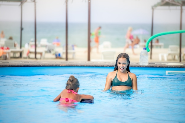 Twee zusjes meisjes zwemmen in een groot zwembad met helderblauw water van mij in de buurt van het hotel op de achtergrond van de zee en het strand. concept vakantie tropisch warm land met kinderen
