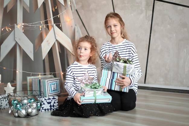 Twee zusjes met kerstcadeaus zitten in een moderne woonkamer.
