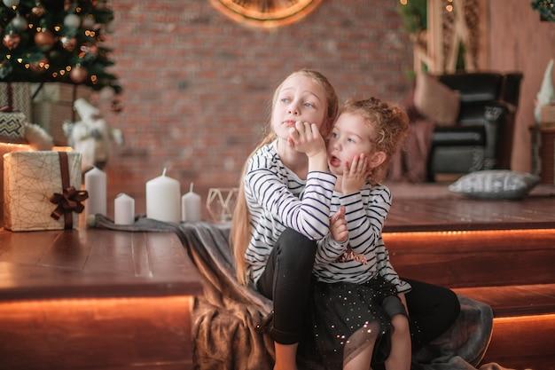 Twee zusjes praten zittend in een gezellige woonkamer