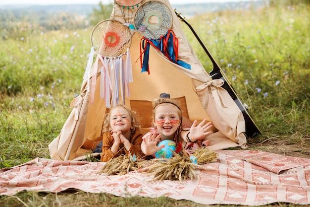 Twee zusjes vermaken zich in de wigwam en spelen indianen. tipi is versierd met dromenvangers en gitaar.