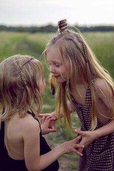 Twee zussen blondjes in een veld worden in de zomer bij indianen gespeeld