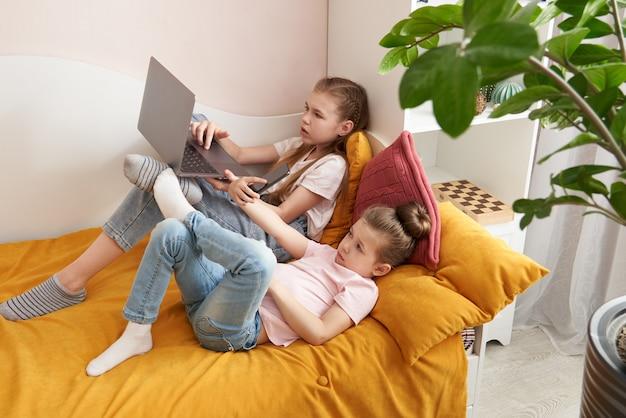 Twee zussen die op een bed liggen die samen laptop met behulp van lettend op iets