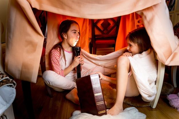 Twee zussen die 's nachts onder deken enge verhalen vertellen telling Premium Foto