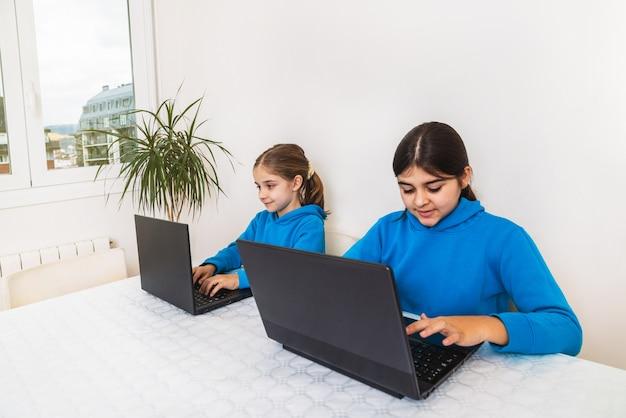 Twee zussen, een blonde en een brunette thuis in schooluniform met blauwe sweater die thuis huiswerk aan het studeren is met laptop
