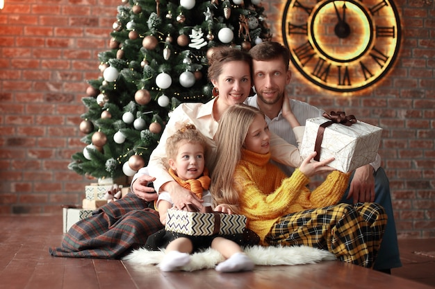Twee zussen en hun ouders zitten bij de kerstboom