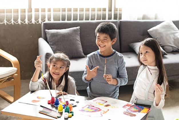 Twee zussen en jonge jongen schilderij water kleur op papier, doning activiteit samen, in de woonkamer, het leren van tijd