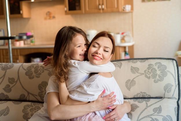 Twee zussen en kleine dochter glimlachen en knuffelen thuis interieur achtergrond.