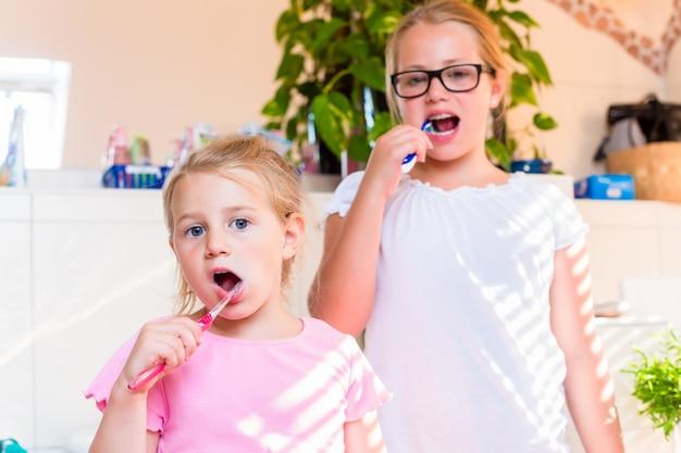 Twee zussen in de badkamer tandenpoetsen