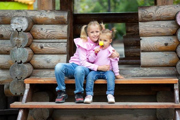 Twee zussen in identieke kleren zitten samen op een houten structuur