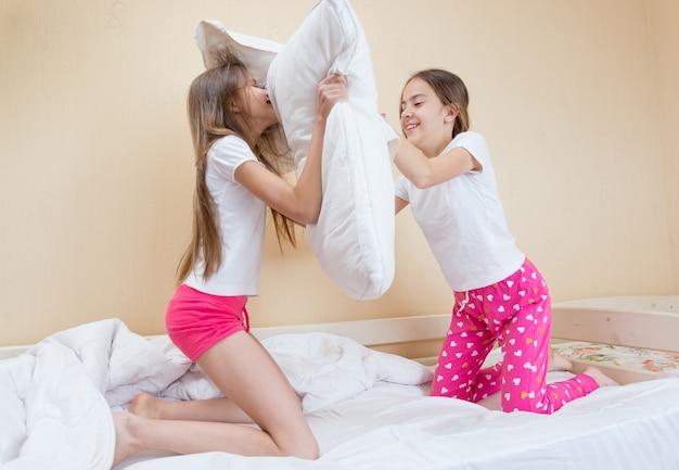 Twee zussen in pyjama die vechten met kussens op bed