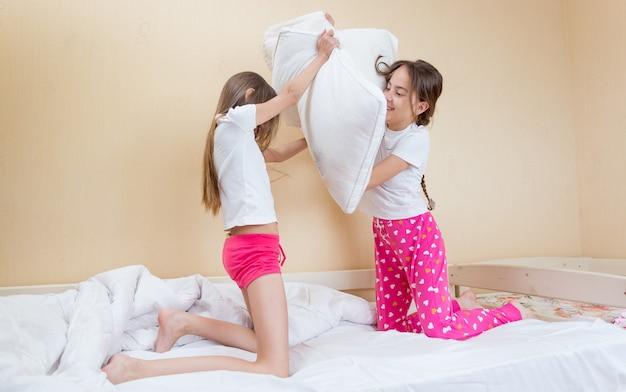 Twee zussen in roze pyjama's vechten met kussens op bed