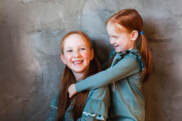 Twee zussen knuffelen, rood haar, sproeten, vreugde, gelach, familie