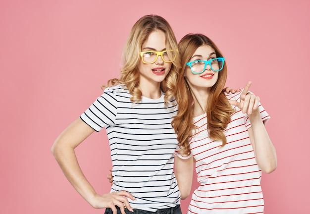 Twee zussen knuffelen samen gestreepte t-shirts vriendschap bijgesneden uitzicht roze muur.