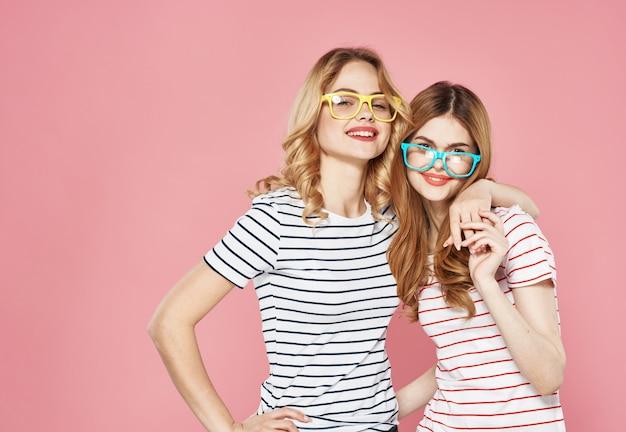 Twee zussen knuffelen samen gestreepte t-shirts vriendschap bijgesneden uitzicht roze.