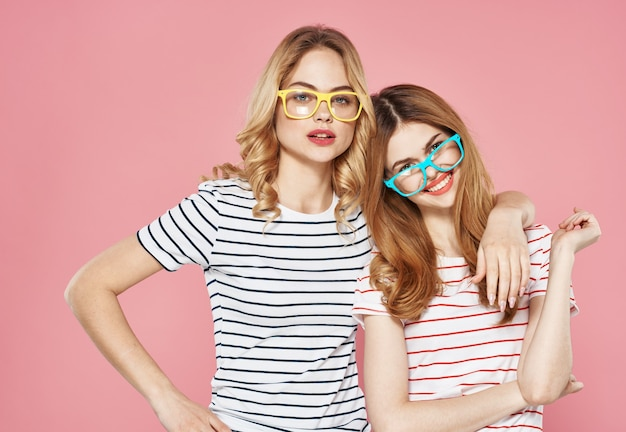 Twee zussen knuffelen samen gestreepte t-shirts vriendschap bijgesneden weergave roze achtergrond