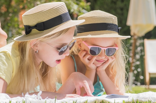 Twee zussen lezen interesseboek in de tuin, zomerpret