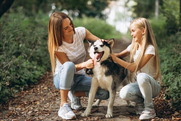Twee zussen met hun hond in park