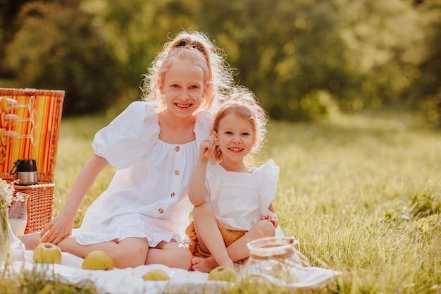 Twee zussen met picknick zittend op het gazon zomerse kopieerruimte