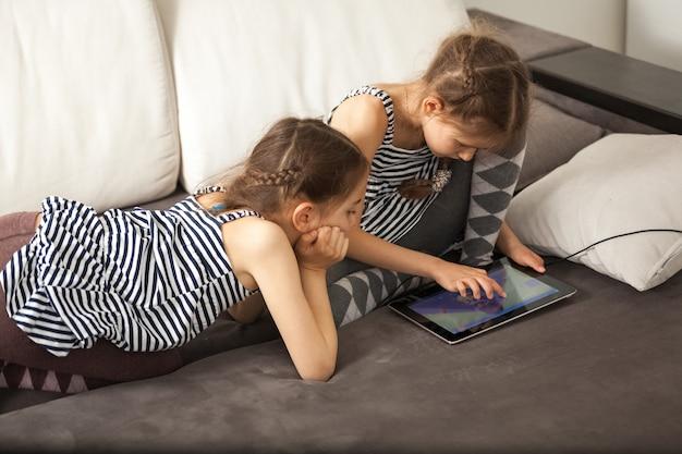 Twee zussen met tablet op de bank thuis
